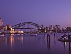 Purple sunset over Sydney Harbour Bridge, Australia on a tranquil summer evening with boat traffic and city lights in a transport and travel concept